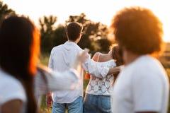 Bedrijf van vrienden in openlucht op een zonnige dag Op de achtergrond omhelst een jonge mens een meisje royalty-vrije stock fotografie