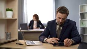 Bedrijfarbeider het typen op laptop, die informatie over tablet zoeken, analyse royalty-vrije stock fotografie