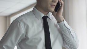 Bedrijfdirecteur die gelukkig na telefoongesprek, voordelige aanbieding kijken stock footage