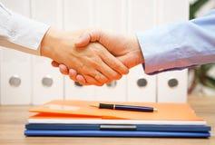 Bedrijfs de man en de vrouw zijn handenschudden binnen over documenten met van Stock Afbeelding