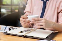 Bedrijfs en financiënconcept, de koffiekop van de Onderneemsterholding en het bespreken van de Grafiek van de verkoopanalyse in k stock afbeelding
