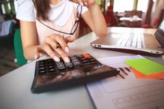 Bedrijfs en financiënconcept de vrouwen werken met calculator en laptop, pen en notitieboekje aan de houten lijst Stock Afbeelding