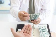 Bedrijfs en financiënconcept, Hand van een zakenman die geld geven aan zijn partner stock fotografie