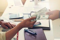 Bedrijfs en financiënconcept, Hand van een zakenman die geld geven aan zijn partner royalty-vrije stock afbeelding