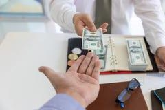 Bedrijfs en financiënconcept, Hand van een zakenman die geld geven aan zijn partner royalty-vrije stock foto