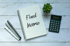 Bedrijfs en financiënconcept Hoogste die mening van installatie, calculator, pen en notitieboekje met Vast Inkomen wordt geschrev stock foto