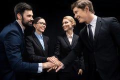 Bedrijfs en handen verbinden stapelen en mensen die geïsoleerd op zwarte glimlachen stock afbeelding