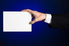 Bedrijfs en reclameonderwerp: Mens die in zwart kostuum een witte lege kaart in zijn hand op een donkerblauwe achtergrond in stud Royalty-vrije Stock Afbeelding
