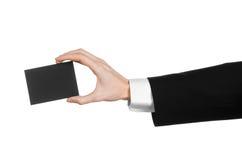 Bedrijfs en reclameonderwerp: Mens die in zwart kostuum een zwarte lege die kaart houden ter beschikking op witte achtergrond in  Stock Foto