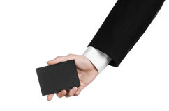 Bedrijfs en reclameonderwerp: Mens die in zwart kostuum een zwarte lege die kaart houden ter beschikking op witte achtergrond in  Royalty-vrije Stock Fotografie