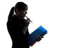 Bedrijfs geconcentreerde vrouw houdend het silhouet van omslagendossiers Stock Foto's