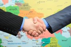 Bedrijfs handdruk over wereldkaart Stock Foto