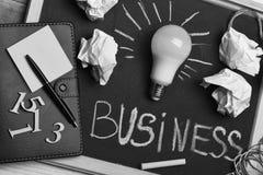 Bedrijfs ideeconcept Bord met gerimpelde document, blocnote, pen, cijfers en lamp royalty-vrije stock afbeelding