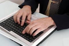 Bedrijfs mens die aan een notitieboekjecomputer werkt Stock Foto's