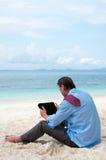 Bedrijfs mens die aan het strand met PC werkt royalty-vrije stock afbeeldingen