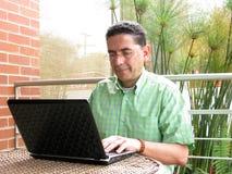 Bedrijfs mens die aan laptop met glazen werkt en sm Stock Afbeeldingen