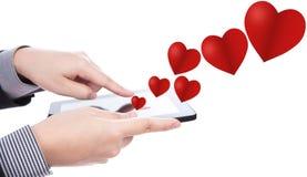 Bedrijfs mens die een apparaat van het aanrakingsscherm met hart met behulp van Stock Afbeeldingen