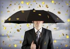 Bedrijfs mens die een paraplu, geld het vallen houdt Royalty-vrije Stock Fotografie