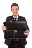Bedrijfs mens die een zwarte aktentas aanbiedt Royalty-vrije Stock Fotografie