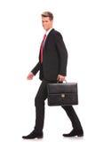 Bedrijfs mens die het korte geval en lopen houden Stock Foto
