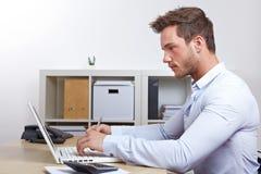 Bedrijfs mens die met laptop werkt stock foto's