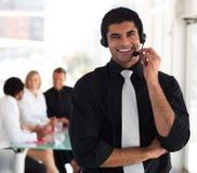 Bedrijfs mens die op een hoofdtelefoon spreekt Royalty-vrije Stock Foto