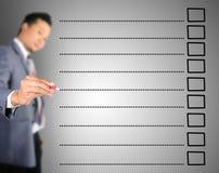 Bedrijfs mens die op lege controlelijst schrijven Stock Foto