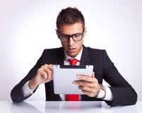 Bedrijfs mens die op zijn elektronisch stootkussen selecteert Stock Fotografie