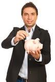 Bedrijfs mens gezet muntstuk aan piggy Stock Foto's