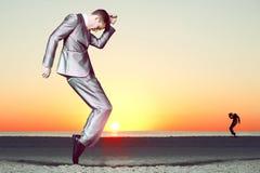 Bedrijfs mens in kostuum dat bij het strand danst. Stock Foto