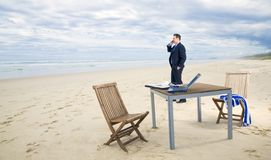 Bedrijfs mens met bureau op het strand Royalty-vrije Stock Afbeeldingen