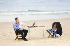 Bedrijfs mens met bureau op het strand Stock Fotografie
