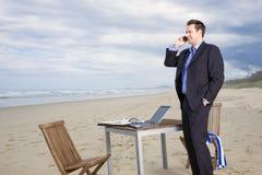 Bedrijfs mens met bureau op het strand Stock Foto's