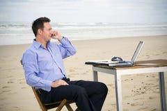 Bedrijfs mens met bureau op het strand Royalty-vrije Stock Foto