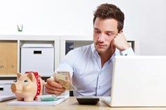 Bedrijfs mens met geld en piggy Royalty-vrije Stock Foto's