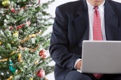 Bedrijfs mens met laptop dichtbij Kerstmisboom Stock Fotografie