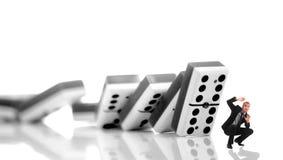 Bedrijfs mens ongeveer die door een domino moet worden verpletterd stock foto's