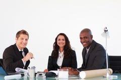 Bedrijfs mensen die aan de camera in een vergadering glimlachen Royalty-vrije Stock Foto