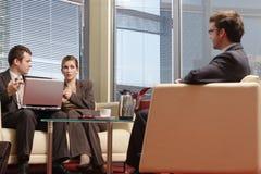 Bedrijfs mensen die in het bureau en het spreken zitten royalty-vrije stock foto's