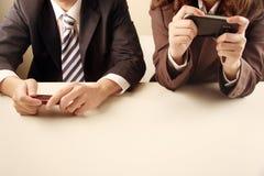 Bedrijfs mensen die mobiele telefoons met behulp van Stock Afbeeldingen