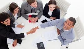 Bedrijfs mensen die terwijl het sluiten van een overeenkomst glimlachen Stock Foto