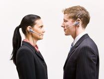 Bedrijfs mensen in hoofdtelefoons die zich van aangezicht tot aangezicht bevinden stock foto