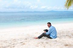 Bedrijfs mensenzitting en het werken aan het strand royalty-vrije stock foto