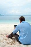 Bedrijfs mensenzitting en het werken aan het strand royalty-vrije stock afbeeldingen