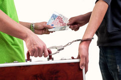 Bedrijfs overdrachtovereenkomst. uitwisseling tussen geld en koffer door hand die met handcuffs wordt gevangen Royalty-vrije Stock Afbeeldingen