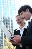Bedrijfs paar dat laptop met behulp van Stock Fotografie