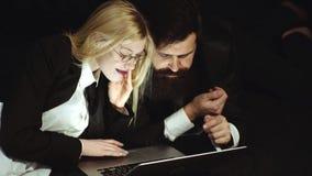 Bedrijfs paar dat laptop met behulp van Geïsoleerde zakenman - knappe man en mooie vrouw op zwarte achtergrond De werkplaats stock footage