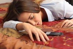 Bedrijfs vermoeide vrouw en slaap in een hotelbed Stock Foto's