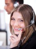 Bedrijfs vrouw die door hoofdtelefoon spreekt Royalty-vrije Stock Foto's