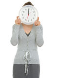 Bedrijfs vrouw die klok voor gezicht toont Royalty-vrije Stock Afbeeldingen